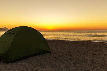 Tent op het strand bij zonsondergang