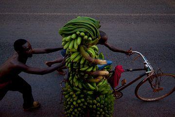 Bananen achterop een fiets in Oeganda, Afrika van Teun Janssen