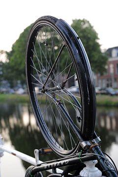 Fietswiel aan hek van gracht in Delft van Mariska van Vondelen