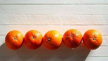Vijf sinaasappels op een rij op een witte houten tafel van