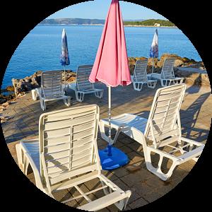 Parasols en ligstoelen op het strand van Krk in het Kroatisch van Heiko Kueverling