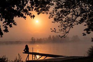 la silhouette d'une femme assise sur la maille au lever du soleil