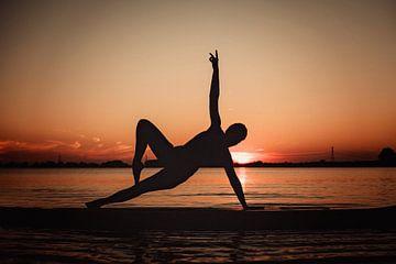 Yogapose als silhoutte tijdens zonondergang van Mijke Bressers