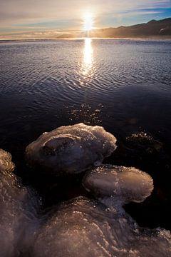 Eisklumpen auf Steinen, Wasser und die aufgehende Sonne von Michael Semenov