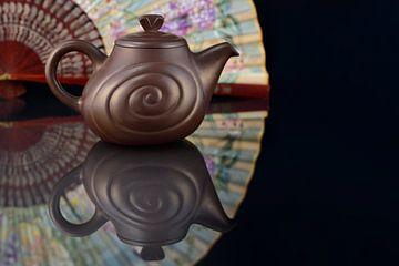 Vieille théière en poterie chinoise devant des éventails sur Ulrike Leone