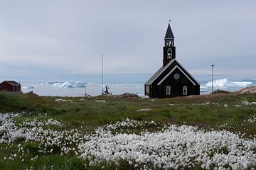 Kerkje in Groenland met bloemen en ijsbergen in de verte. van Ralph Rozema
