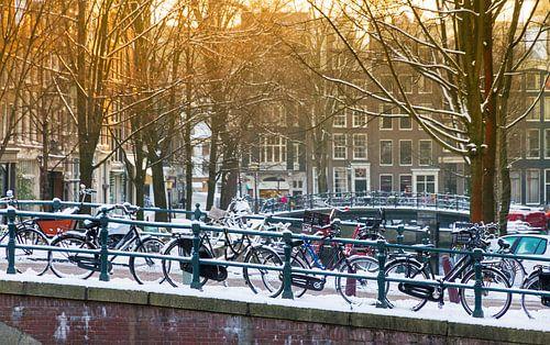 Fietsen op de brug in Amsterdam van Dennis van de Water