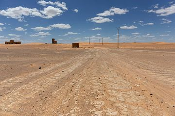 Een onverharde weg leidt door Noord-Sahara woestijnlandschap, Afrika van Tjeerd Kruse