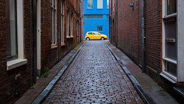 Gele auto tegen blauwe muur van Idema Media