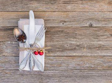 Het dinerplaats van het Kerstmenu met bestekreeks, servet en decoratie van Alex Winter