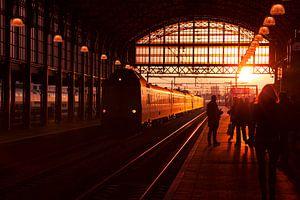 Silhouetten van wachtende reizigers op treinstation tijdens zonsondergang