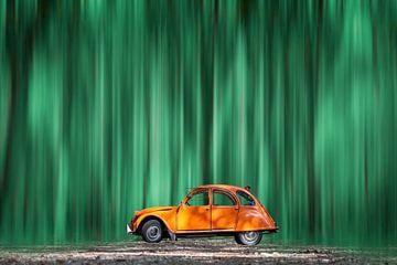 Orangefarbener Citroën 2CV in einem grünen Wald