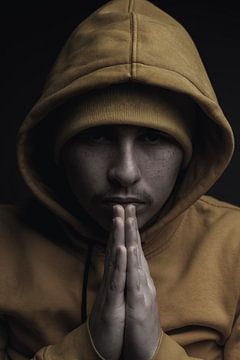 Portret Jonge man met capuchon knijpt handen ineen van Besa Art