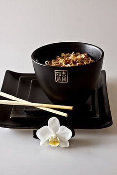 zwarte Chinese kom en gestapelde borden met eetstokjes en orchidee als detail gevuld met noodles als van