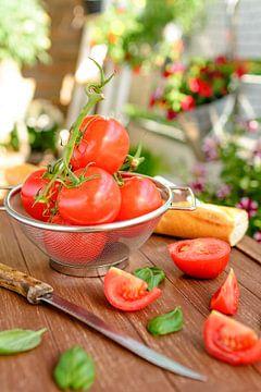 Frische Tomaten liegen in einem Küchensieb auf einem Holztablett. von Edith Albuschat