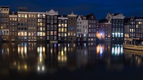 Damrak Amsterdam in de avond van