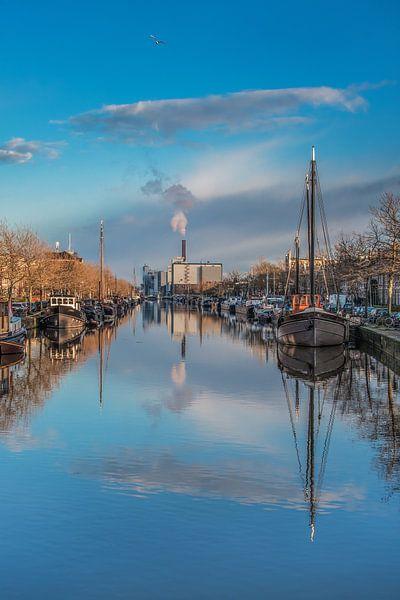 De Emmakade in de herfst met de schepen en wolken gereflecteerd. van Harrie Muis