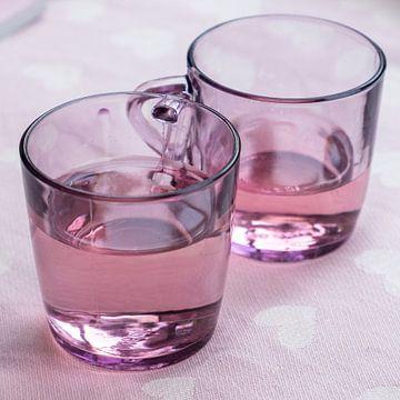 Satz rosa Teegläser mit Flüssigkeit für einen besonders rosa Hintergrund mit weißen Herzen von Idema Media