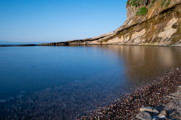 stijle rotswand in de zee met spiegelend water von Eline Oostingh
