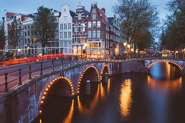 Beleuchtete Brücken über die Grachten von Amsterdam an einem Sommerabend