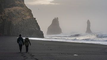 Touristen machen einen Spaziergang am Strand von Reynisdrangar im Süden Islands in der Nähe von Vik von Anges van der Logt