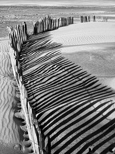 Schaduw van houten hekwerk op strand van