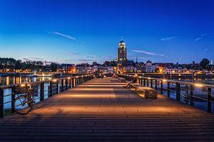 Iemand kijkt naar Deventer tijdens het blauwe uur aan de IJssel.