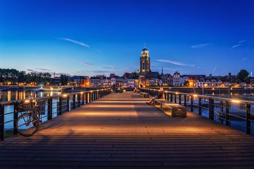 Iemand kijkt naar Deventer tijdens het blauwe uur aan de IJssel. van Bart Ros
