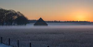 Winterse zonsopkomst met een schuur in de mist