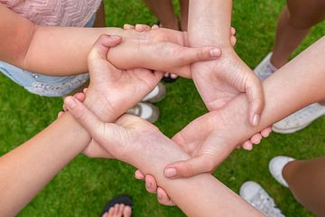 Handen van kinderen pakken elkaar bij polsen van
