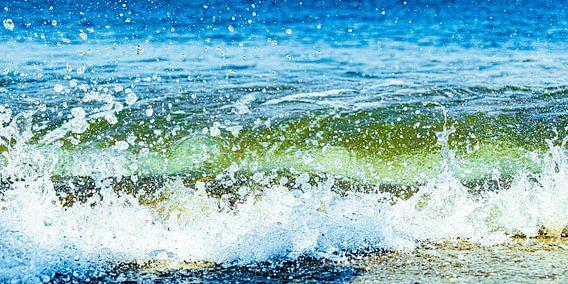 Opspattend zee water van een golf op het strand van Scheveningen