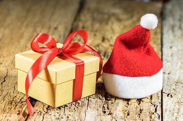 Kerstcadeau met strik en rode kerstmuts van Alex Winter
