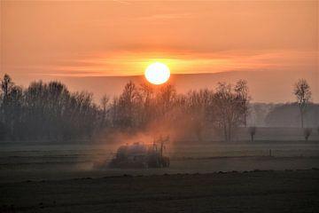 Een boer rijdt gier uit over het weiland bij ondergaande zon van Susan Dekker