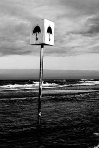Schwarz-Weiß-Foto eines Schildes mit Regenschirm am Strand