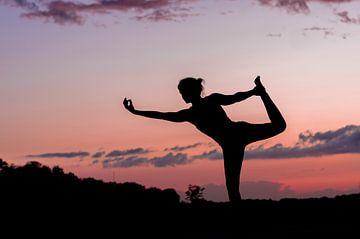 Silhouette van een yoga lerares in pose bij ondergaande zon. van Manon Moller Fotografie