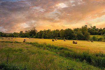 Landschap met hooibalen tijdens zonsondergang van Kok and Kok