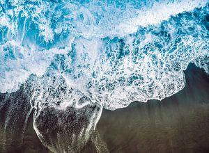 Branding van de blauwe zee op het zwarte vulkaanstrand