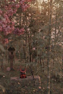 Samurai Helm und Katana Schwert liegen auf einem alten Stein in einem friedlichen Wald von Besa Art