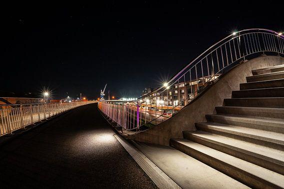 Verlicht voetpad met trappen en hekwerk en uitzicht over haven van Harlingen