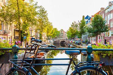 Altes Fahrrad an einer Gracht in Amsterdam von Werner Dieterich