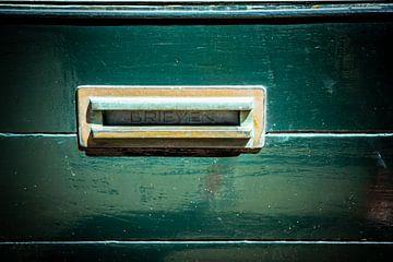 Sierlijke brievenbus in een oude groene houten deur, traditionele manier om brieven aan een huis te
