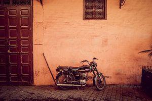 Vintage brommer tegen rode muur in Marrakesh van Rob Berns