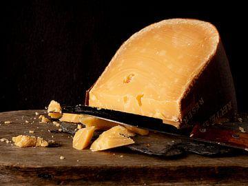 Alter zerbröckelter Käse auf Holzplanke von simone swart