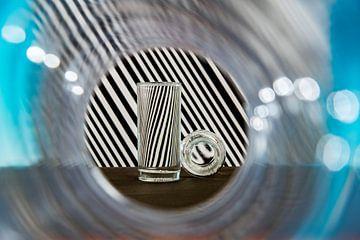 Glaswerk tegen een zwart-wit gestreepte achtergrond van Wim Stolwerk
