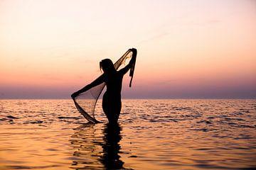 Naakte vrouw met een visnet bij ondergaande zon in de waddenzee