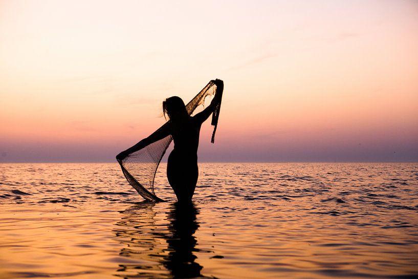 Naakte vrouw met een visnet bij ondergaande zon in de waddenzee van Arjan Groot
