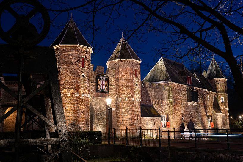 De verlichte koppelpoort van Amersfoort tijdens een sfeervolle avond in het blauwe uur. van Fotografiecor .nl