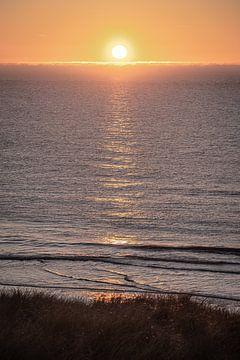 Zonsondergang met mistige omstandigheden op zee en reflectie van Rutger van der Klip