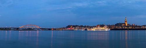Groot wijds panorama van Nijmegen en de Waalbrug bij nacht van