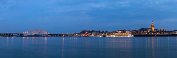 Groot wijds panorama van Nijmegen en de Waalbrug bij nacht